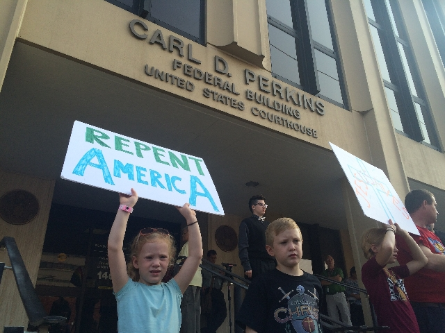 Supporters hold signs outside federal court in Ashland, Kentucky, on Thursday, Sept. 3, 2015. Rowan County Clerk Kim Davis was held in contempt of court after she refused a Supreme Court ruling sa ...