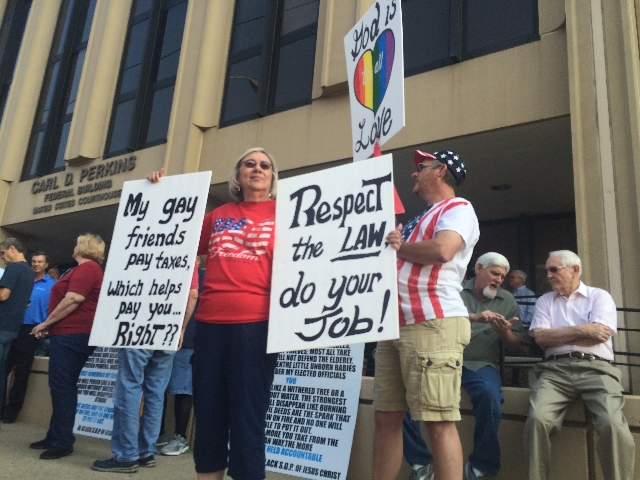 Supporters hold signs and flags outside federal court in Ashland, Kentucky, on Thursday, Sept. 3, 2015. Rowan County Clerk Kim Davis was held in contempt of court after she refused a Supreme Court ...