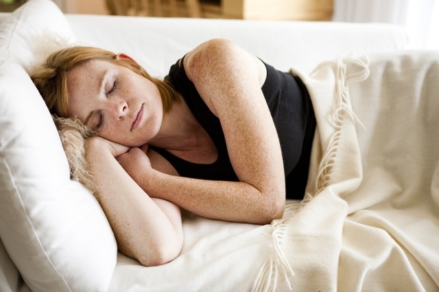 FILE- Stock image of a woman sleeping on the couch. (Amanda Greene/CNN)