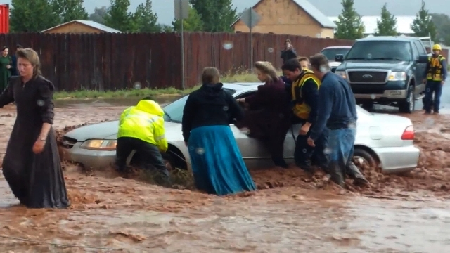 Fire and rescue workers pull a woman from a car in knee-deep flood water in the town of Hildale, Utah, along the Arizona border on Monday, Sept. 15, 2015. (CNN)
