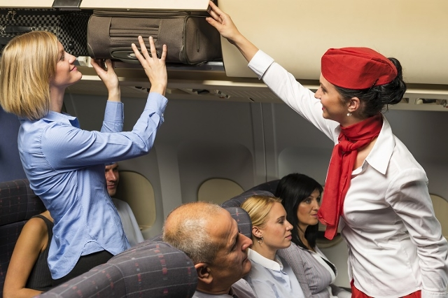 Flight attendant help passenger with luggage cabin (Thinkstock)