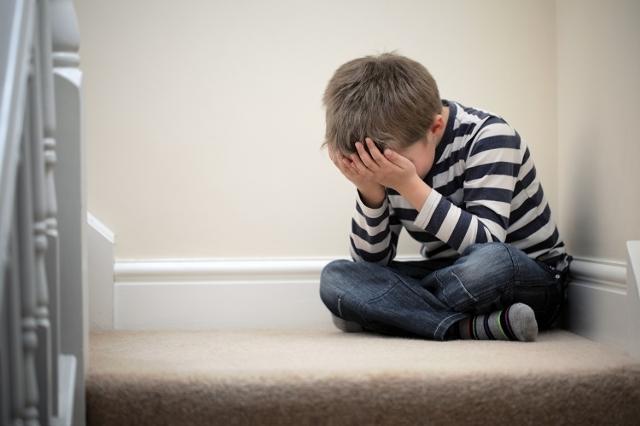 Upset child sitting on staircase (Thinkstock)