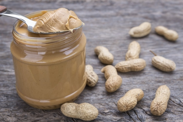 Jar of peanut butter with nuts.