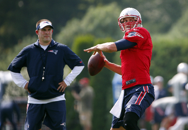 Jul 30, 2015; Foxborough, MA, USA; New England Patriots quarterback Tom Brady (12) throws as offensive coordinator Josh McDaniels looks on during training camp at Gillette Stadium. (Winslow Townso ...