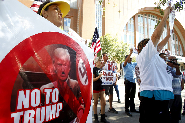 Protestor Genoveva Castillos holds a sign outside of a political rally for Republican presidential candidate Donald Trump in Dallas, Sept. 14, 2015.  (Mike Stone/Reuters)