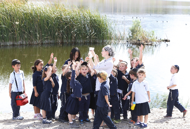 Kindergarten and first grade students from Yeshiva Day School in Las Vegas listen to their teacher Devorah Locker, center, as she explains how to test water during their science field trip at Corn ...