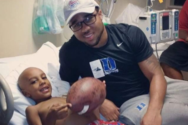 Former Bishop Gorman High star and now Duke senior running back Shaquille Powell presents his brother, Malachi Briggs, the game ball from Duke's win against Virginia last season. Malachi die ...