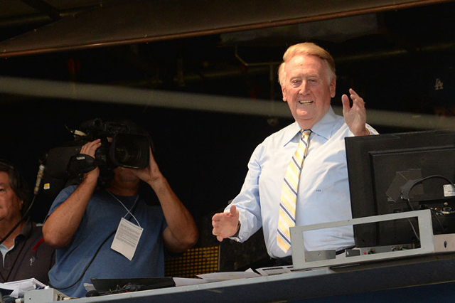 Los Angeles Dodgers announcer Vin Scully gets applause from the crowd after it was announced he would return to Dodgers booth for a 66th year during the game against the Atlanta Braves at Dodger S ...