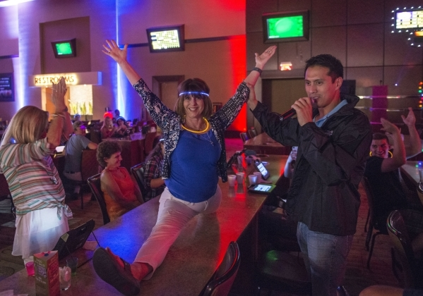 From left, Monica Lewis watches Susan Riffle do a split as Bryan Chan, the emcee, holds her hand during Rocket Bingo at Red Rock Resort in Las Vegas on Thursday, Aug. 27, 2015. Rocket Bingo featur ...