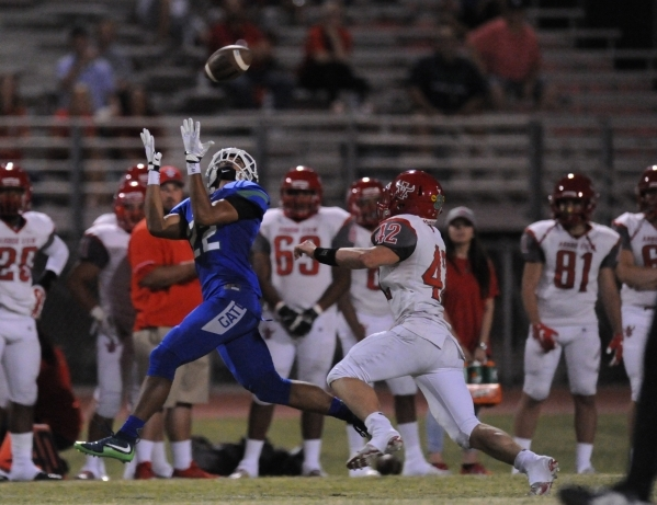 Green Valley wide receiver Brayon Williams catches a pass as Arbor View safety Andrew Wagner (42) defends in the second quarter of their high school football game at Green Valley High School in He ...