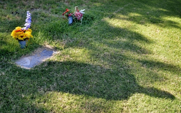 The shadow of Clark County Coroner John Fudenberg falls across the grave of a person who was originally buried as unknown deceased at the Woodlawn Cemetery at 1500 Las Vegas Blvd. North in Las Veg ...