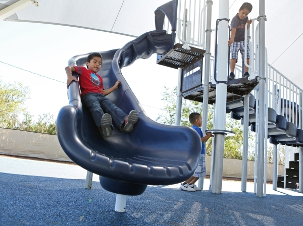 Robert Herrera, 7, left, goes down the slide at the newly renovated Joe Kneip Park Thursday, Sept. 17, 2015, in North Las Vegas. Community members, local politicians and sponsors celebrated a gran ...