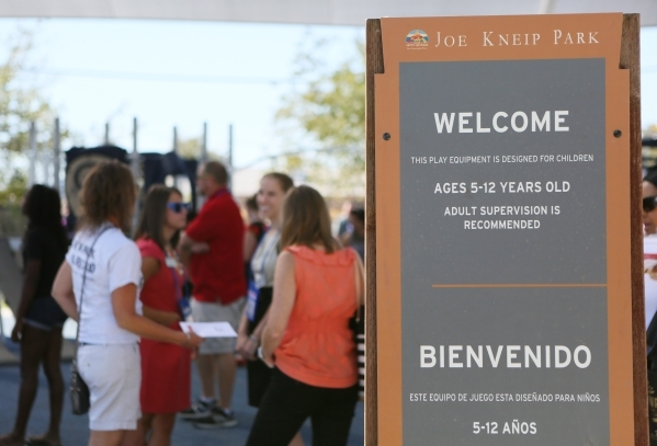 People socialize near a sign at the newly renovated Joe Kneip Park Thursday, Sept. 17, 2015, in North Las Vegas. Community members, local politicians and sponsors celebrated a grand reopening of t ...