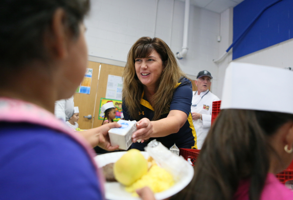 Patty Charlton, College of Southern Nevada senior vice president of strategic initiatives and administrative services, serves milk to students during a Chefs for Kids complementary breakfast at Lo ...