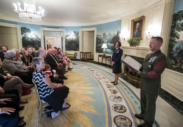 """Col. Nicole Malachowski, left, participates in her colonel """"frocking"""" ceremony with Master Gunnery Sgt. William Mahoney in the Diplomatic Reception Room of the White House, Sept. 16, 201 ..."""