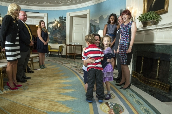 Col. Nicole Malachowski hugs her 5-year-old twins, Garrick and Norah, as her parents, Robert Ellingwood and Catherine Elingwood, and First Lady Michelle Obama look on during her promotion ceremony ...