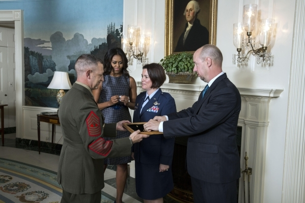 Col. Nicole Malachowski, second from right, receives her colonel pin from Master Gunnery Sgt. William Mahoney, left, in the Diplomatic Reception Room of the White House, Sept. 16, 2015. Looking on ...