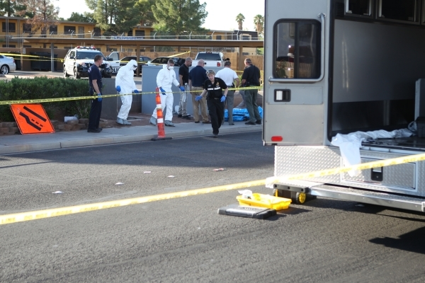 Las Vegas police investigate the scene where a body found inside a water vault in front the The Suites apartments near the intersection of S. Nellis Boulevard and E. Flamingo Road in Las Vegas Tue ...