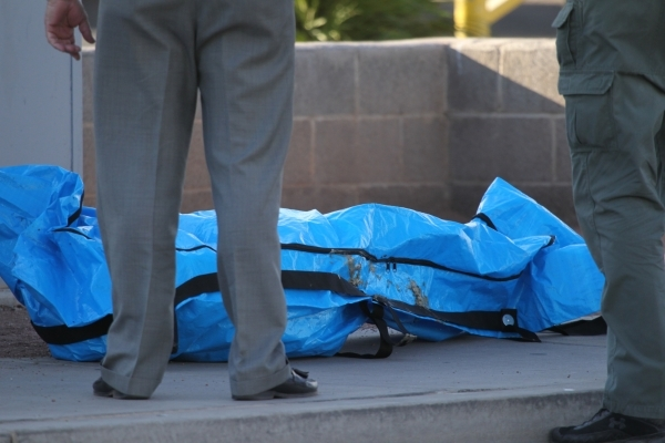 Las Vegas crime scene investigators stand over a body found inside a water vault in front of The Suites apartments near the intersection of S. Nellis Boulevard and E. Flamingo Road in Las Vegas Tu ...