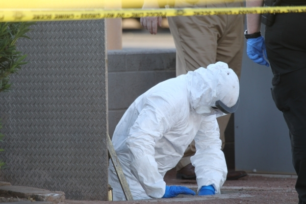 A Las Vegas crime scene investigator exits a water vault where a body was found in front of The Suites apartments near the intersection of S. Nellis Boulevard and E. Flamingo Road in Las Vegas Tue ...