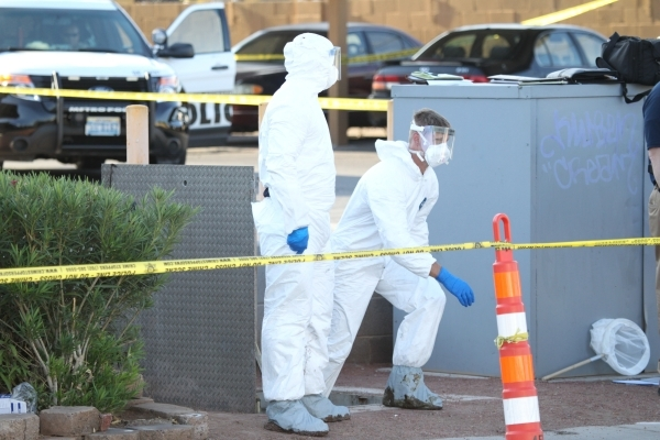 Las Vegas crime scene investigators exit a water vault where a body was found in front of The Suites apartments near the intersection of S. Nellis Boulevard and E. Flamingo Road in Las Vegas Tuesd ...
