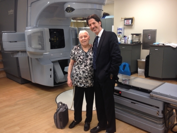 Patient Elnora Walters poses for a photo with Dr. Brian Lawenda at 21st Century Oncology. Walters wears Optune, a noninvasive medical device that sits on the patient's head like a swim cap.  ...