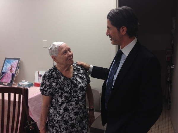 Patient Elnora Walters looks up at Dr. Brian Lawenda, board certified radiation oncologist at 21st Century Oncology.  Walters wears Optune, a noninvasive medical device that sits on the patient&ls ...