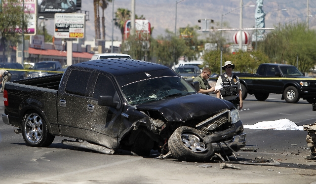 A body lays on the ground in on the westbound side of Sahara Avenue near Valley View Boulevard in Las Vegas on Sunday, July 20, 2014. Two cars were involved in a wreck that resulted in the fatal a ...