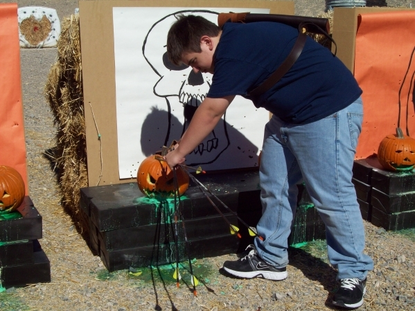 A participant is seen taking an arrow out of a pumpkin during the 2012 Pumpkin Smash at the County Shooting Complex, 11357 N. Decatur Blvd. This year's event is set for Oct. 31. (Special to  ...