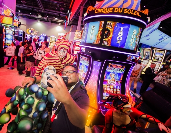 Vander McInnis of Snoqualmie, Wash.  takes a selfie with  Cirque du Soleil performers in front of the newest Cirque du Soleil-themed slots at Scientific Games booth during the Global Gaming Expo a ...
