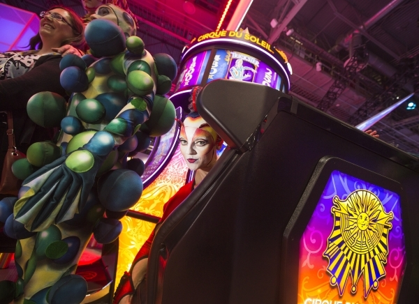 A Cirque du Soleil performer peers around a chair in front of the newest Cirque du Soleil themed slots at Scientific Games booth during the Global Gaming Expo at the  Sands Expo and Convention Cen ...