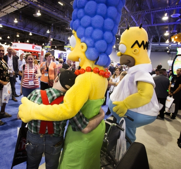Joe Manee hugs a Marge Simpson character at the Simpson-themed slots at Scientific Games booth during the Global Gaming Expo at the  Sands Expo and Convention Center on Tuesday, Sept. 29,2015. (Je ...