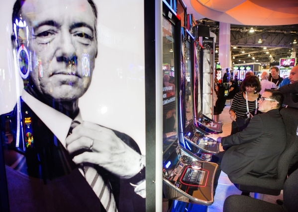 An image of actor Kevin Spacey is seen in front of a row of  House of Cards gaming machines in the International Game Technology booth at the Global Gaming Expo in the Sands Expo and Convention Ce ...