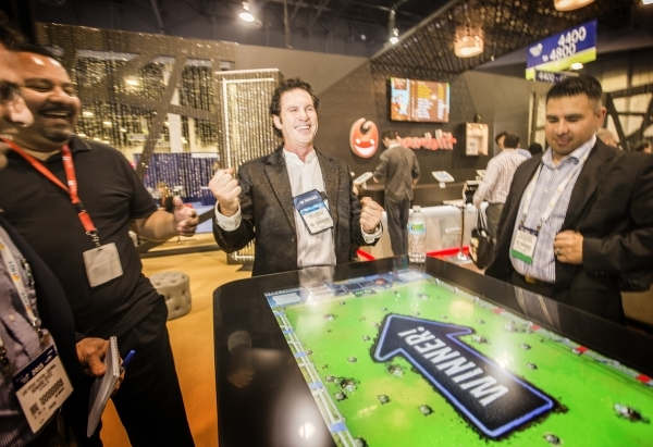 Eric Meyerhofer, center, CEO of Gamblit Gaming, celebrates after winning on a tabletop skill-based game in the Gamblit booth at the Global Gaming Expo in the Sands Expo and Convention Center on We ...