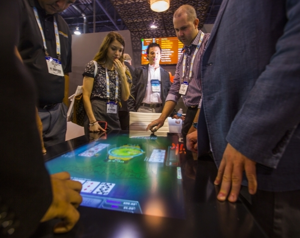 Eric Meyerhofer, center, CEO of Gamblit Gaming, watches people play a tabletop skill-based game in the Gamblit booth at the Global Gaming Expo in the Sands Expo and Convention Center on Wednesday, ...