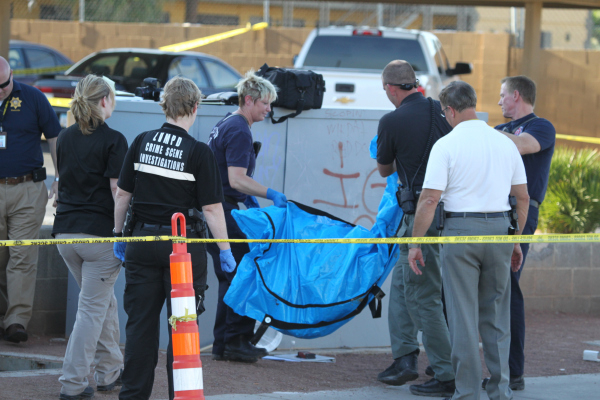 Las Vegas crime scene investigators transport a body found inside a water vault in front of The Suites apartments near the intersection of S. Nellis Boulevard and E. Flamingo Road in Las Vegas Tue ...