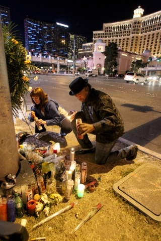 Tehran Bolden, brother of  cabbie Michael Boldon, 62, whose cab exploded upon impact last week -- the result of a car crash triggered by a shooting -- lights candles on Las Vegas Boulevard at Flam ...