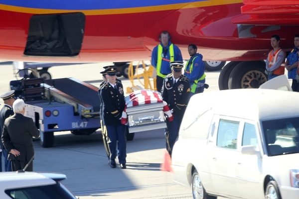 The remains of Las Vegan Sean Wayne Wells, 35, a sergeant first class assigned to the 2nd Battalion, 3rd Special Forces Group, are unloaded from a Southwest Airlines jet during a honorable transfe ...
