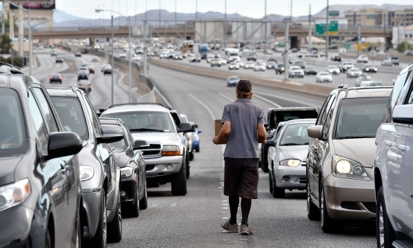 A pan handlers walks along exiting car at Tropicana Avenue on Monday, Sept. 28, 2015, in Las Vegas. David Becker/Las Vegas Review-Journal