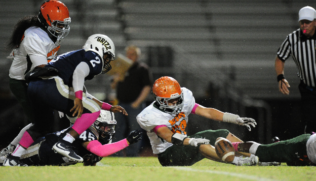 Mojave Rattlers linebacker Wesley Patton, center, and Spring Valley Grizzlies running backs Earnest Wilbert (2) and running back Clark Genneken attempt to recover a Grizzlies fumble in the first q ...