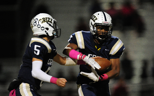 Spring Valley Grizzlies quarterback K.C. Moore (5) hands off to  running back Marcus Dawson (7) against Mojave in the third quarter of their prep football game at Spring Valley High School in Las  ...