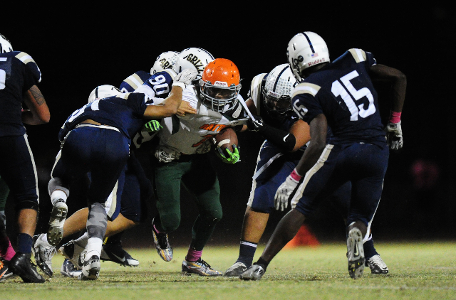 The Spring Valley defense wraps up Mojave running back Khalid Walker, center, in the third quarter of their prep football game at Spring Valley High School in Las Vegas Friday, Oct. 2, 2015. Mojav ...