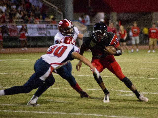 Las Vegas High School quarterback Zach Matlock (12) attempts to break tackles from Corey Leuschner (30) and Zacari Holbert (24) during their prep football game at Las Vegas High School on Friday,  ...