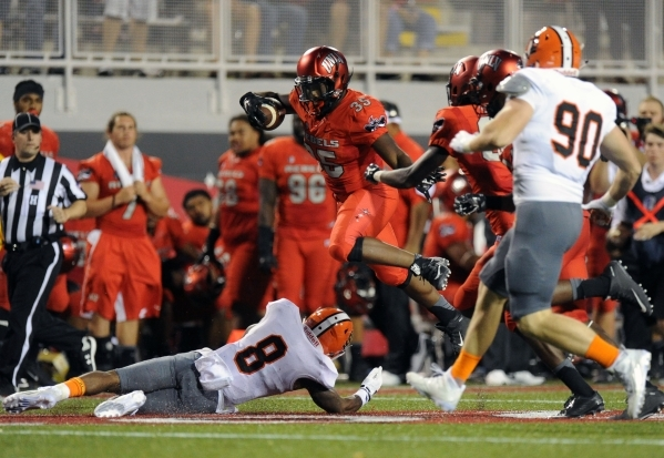 UNLV Rebels running back Xzaviar Campbell (35) jumps over Idaho State Bengals defensive back Erik Collins (8) while rushing the ball in the first half of their NCAA Football game against Idaho Sta ...