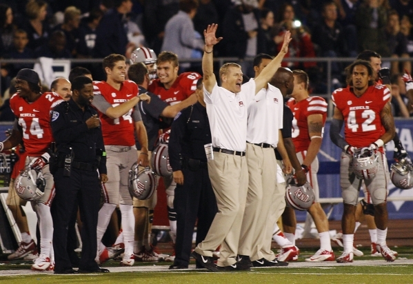 UNLV head coach Bobby Hauck, middle in white, raises his hands in victory as the clock winds down against UNR at Mackay Stadium in Reno on Oct. 26, 2013. (Jason Bean/Las Vegas Review-Journal)