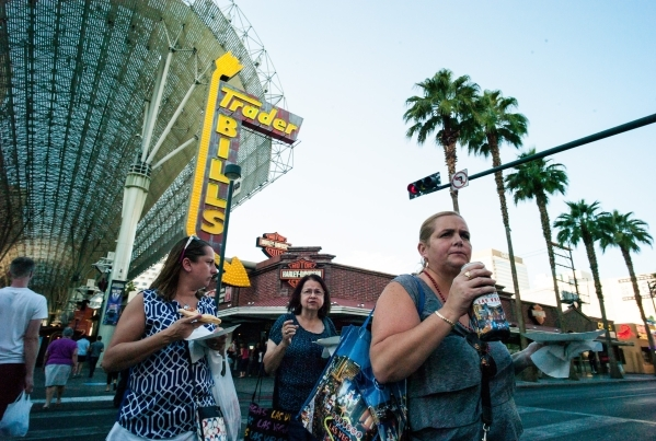 People, holding plates of pizza, walk across Fourth Street at Fremont Street in downtown Las Vegas on Thursday, Oct. 1, 2015. Chase Stevens/Las Vegas Review-Journal Follow @csstevensphoto
