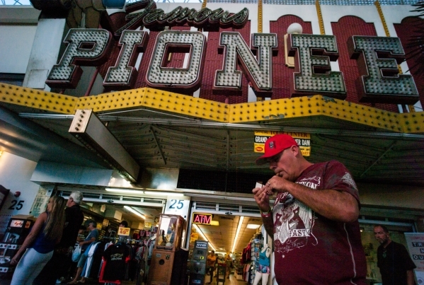 A man lights a cigar at the Fremont Street Experience in downtown Las Vegas on Thursday, Oct. 1, 2015. Chase Stevens/Las Vegas Review-Journal Follow @csstevensphoto