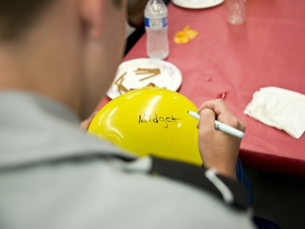 Noah Cosgrove, a freshman at Valley High School, writes a word that bullies have called him onto a balloon he will stomp during a Week of Respect event at Valley High School on Thursday, Oct. 1, 2015.