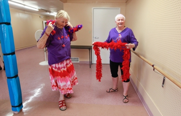 Eighty-four-year-old Paulisca Buckholz, left, and Judy England, 73, put on feather boas at the start of a burlesque dance class at Derfelt Senior Center in Lorenzi Park in Las Vegas on Thursday, O ...