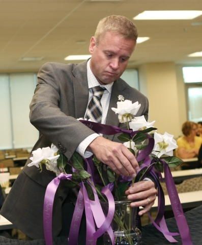 Undersheriff Kevin McMahill places a rose in a vase to honor domestic violence victim´s life during a ceremony in honor and remembrance of victims hosted by the Las Vegas Metropolitan Police Depa ...